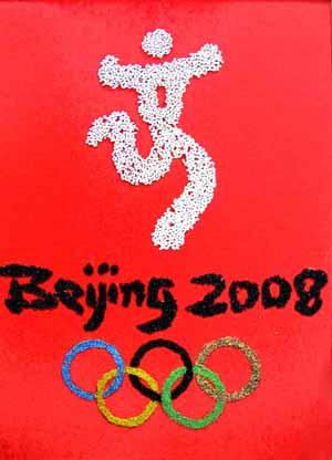 王生俊和老伴用五谷杂粮和碎石子制作了奥运会徽标和火炬