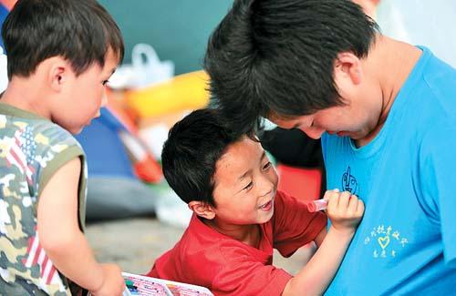 一名来自北川县的儿童在一名志愿者的衣服上画画.