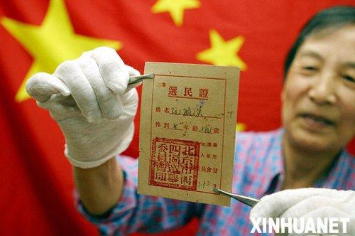 2006年10月13日,北京西城区砖塔社区的阮毓英老人在展示自己珍藏的1953年领取的选民证。新华社发(资料照片)