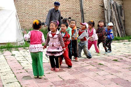 当礼县湫山乡新蕾幼儿园的孩子们沐浴着晨光,唱着儿歌来到学校时