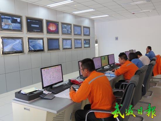 工作人员正在中央控制室操作电脑(图)