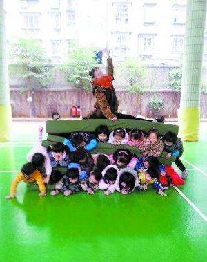 幼儿 老师/由垫子隔开,上下三排孩子,最上面还压着一女老师,秀着一字马...