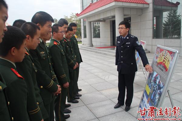 图为宣传民警向军车驾驶员讲解交通事故案例展板