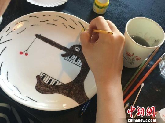 """图为参与者在盘子上作画。崔琳摄   中新网兰州4月20日电(记者崔琳 魏建军)时逢毕业季,就读于西北师范大学美术专业的大四女生梁丰婷开始着手创作""""青春纪念盘"""",即:用陶瓷颜料在白色陶瓷盘上绘制风格不同的图案。随后,这些盘子将作为她的毕业作品展示出来。   """"作画不一定都得在纸张上,也可以在杯子、盘子、陶瓷罐、扇子上……选择不同的绘画材料作画,能够增加绘画的乐趣。""""梁丰婷手绘""""青春纪念盘""""的事迹很快在校园、微"""