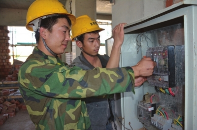 工地电工王江(左)
