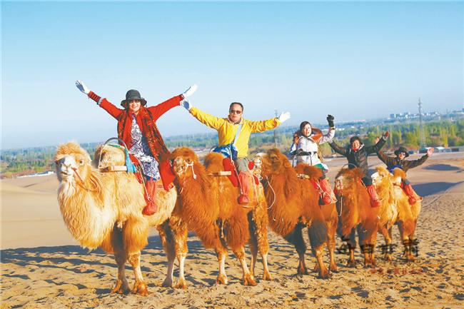 游客骑骆驼畅游敦煌鸣沙山 欣赏大漠风光