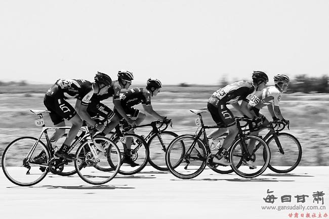 【图片新闻】环湖赛选手在民勤县腾格里沙漠沿沙公路上飞驰
