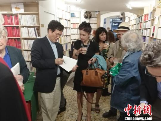 2018年6月在巴黎举办法译诗集《疼痛》首发式上为读者签名。 受访者供图。 供图 摄