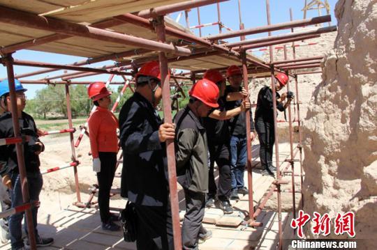 图为设计、施工、监理单位现场探讨破城子遗址保护修复问题。 王建荣 摄