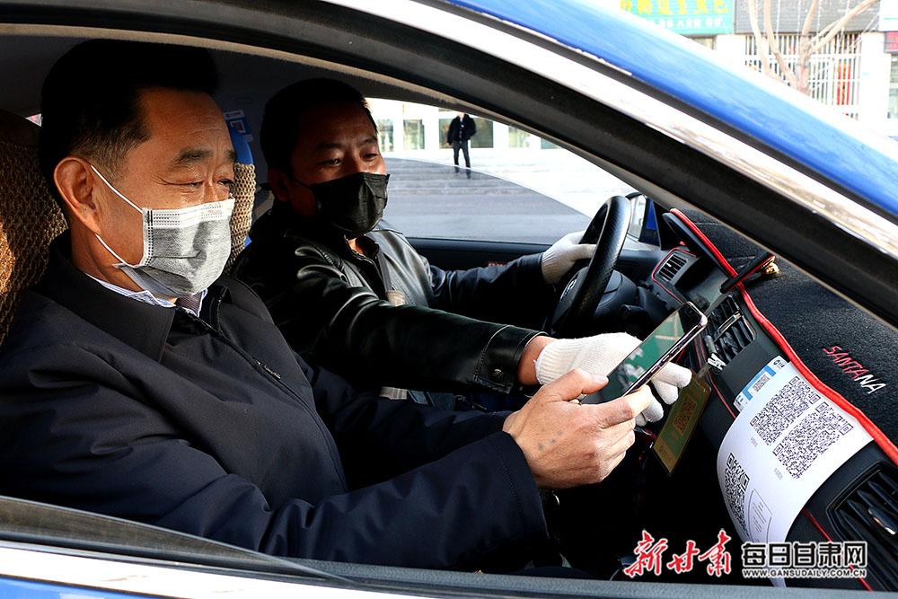 瓜州县出租车司机正在引导乘客扫码登记(鲁晓萍摄).jpg