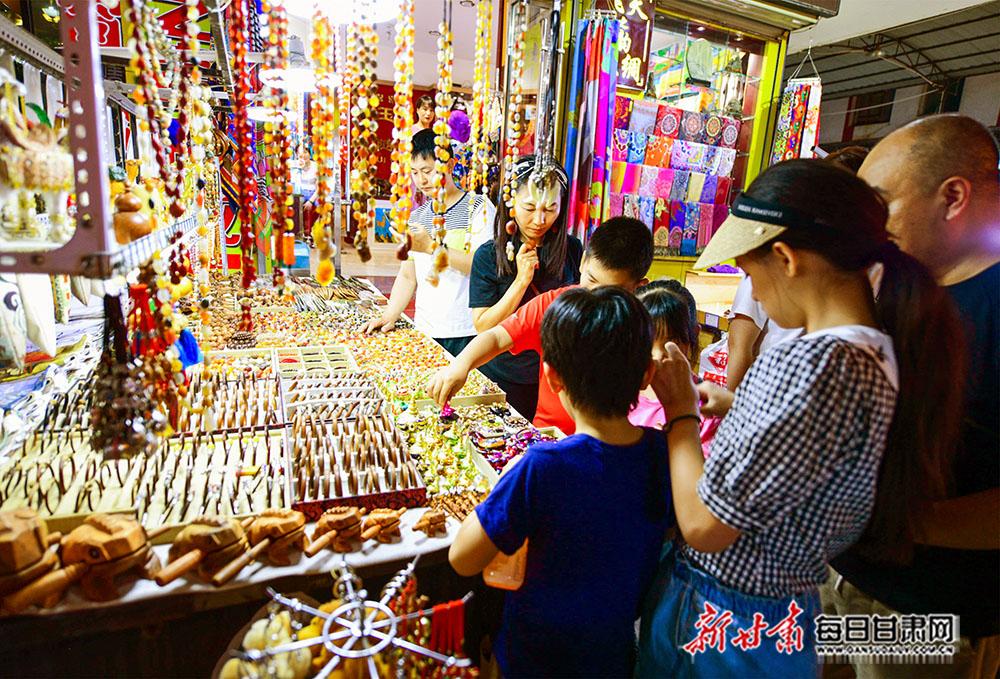 7月29日,游客在敦煌夜市上购买敦煌旅游工艺品。.jpg