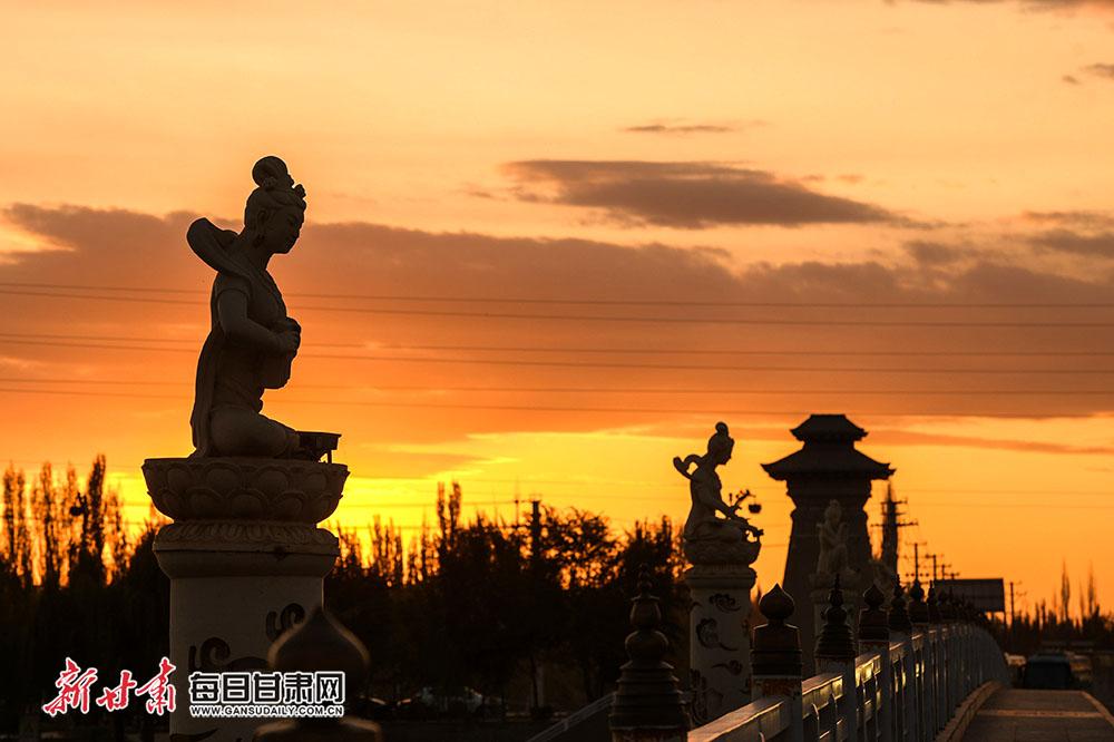 敦煌白马塔大桥上伎乐天雕塑在夕阳的映衬下显得格外神秘,一种宁静、安详的艺术氛围在夕阳下弥漫开来。.jpg
